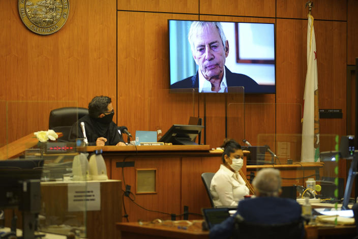A TV still frame of Robert Durst appears on a screen in the courtroom as Deputy District Attorney John Lewin begins opening statements in trial of Durst, a real estate scion charged with murder of his longtime friend Susan Berman, in Los Angeles County Superior Court, Tuesday, May 18, 2021, in Inglewood, Calif. Durst has pleaded not guilty to killing his best friend, Berman, in 2000 at her Los Angeles home. Durst's murder trial was delayed more than a year due to the Covid-19 pandemic. (Al Seib/Los Angeles Times via AP, Pool)