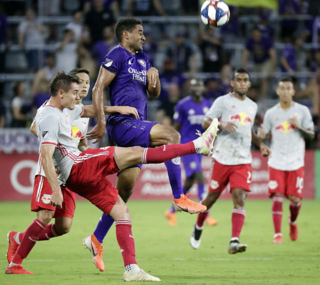 New York Red Bulls' Aaron Long, front left, clears the ball in front of Orlando City's Tesho Akindele, center, during the first half of an MLS soccer match, Sunday, July 21, 2019, in Orlando, Fla. (AP Photo/John Raoux)