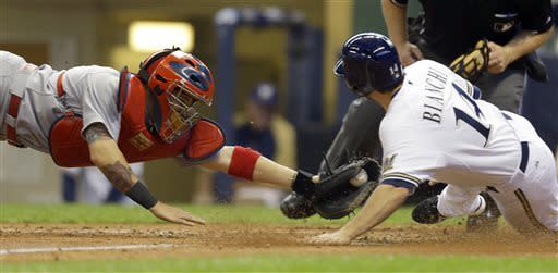 Milwaukee Brewers' Jeff Bianchi, right, scores ahead of the tag by St. Louis Cardinals' Yadier Molina during the eight inning of a baseball game Saturday, May 4, 2013, in Milwaukee. (AP Photo/Jeffrey Phelps)