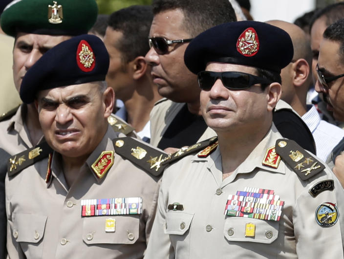 FILE - In this Friday, Sept. 20, 2013 file photo, Egypt's Defense Minister Gen. Abdel-Fattah el-Sissi, center, Egyptian Prime Minister Hazem el-Beblawi, right, and army's Chief of Staff Lt. Gen. Sedki Sobhi, left, attend the funeral of Giza Police Gen. Nabil Farrag in Cairo, Egypt. The head of Egypt's military, Abdel-Fattah el-Sissi, is riding on a wave of popular fervor that is almost certain to carry him to election as president. Unknown only two years ago, a broad sector of Egyptians now hail him as the nation's savior after he ousted the Islamists from power, and the state-backed personality cult around him is so eclipsing, it may be difficult to find a candidate to oppose him if he runs. Still, if he becomes president, he faces the tough job of ruling a deeply divided nation that has already turned against two leaders. (AP Photo/Hassan Ammar, File)