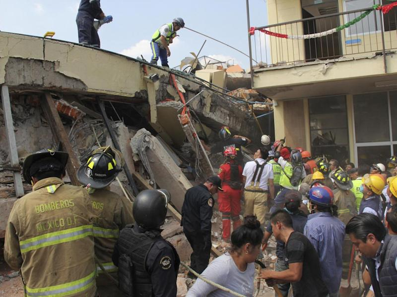 Rescue workers search for children trapped inside the collapsed Enrique Rebsamen school in Mexico City (Carlos Cisneros/AP)