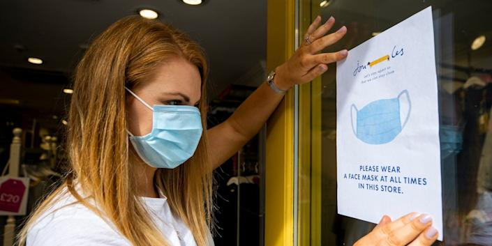 Joanne Millar store manger of Joules in Belfast places a sign in the shop window advising customers that face masks must be worn at all times as face coverings are now compulsory for shoppers.