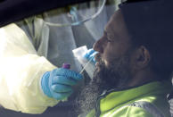 Medical staff take a COVID-19 test from a visitor to a drive through community based assessment centre in Christchurch, New Zealand, Thursday, Aug. 13, 2020. Health authorities in New Zealand are scrambling to trace the source of a new outbreak of the coronavirus as the nation's largest city, Auckland, goes back into lockdown. (AP Photo/Mark Baker)