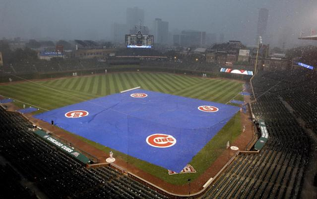 Tarp cover the field during a rain delay in the second inning of the Baltimore Orioles Chicago Cubs an interleague baseball game in Chicago, Saturday, Aug. 23, 2014. (AP Photo/Nam Y. Huh)