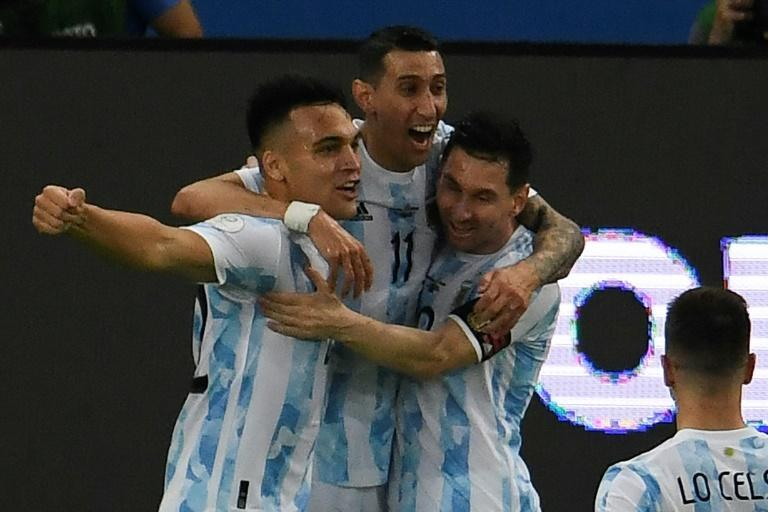 Lautaro Martinez (left) celebrates with his Argentina teammates Angel Di Maria (center) and Lionel Messi (right) after opening the scoring against Venezuela (AFP/MAURO PIMENTEL)