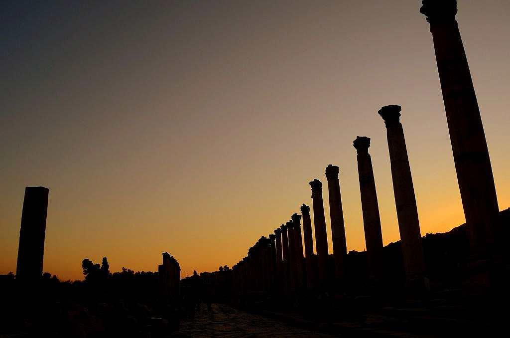 It is almost evening as the tour of Jerash ends. The bagpipers have just begun their melody and the auditorium is packed. Elsewhere, evening lights glow as the sun sets on the ancient site. The columns stand tall, reaching out to the twilight sky.