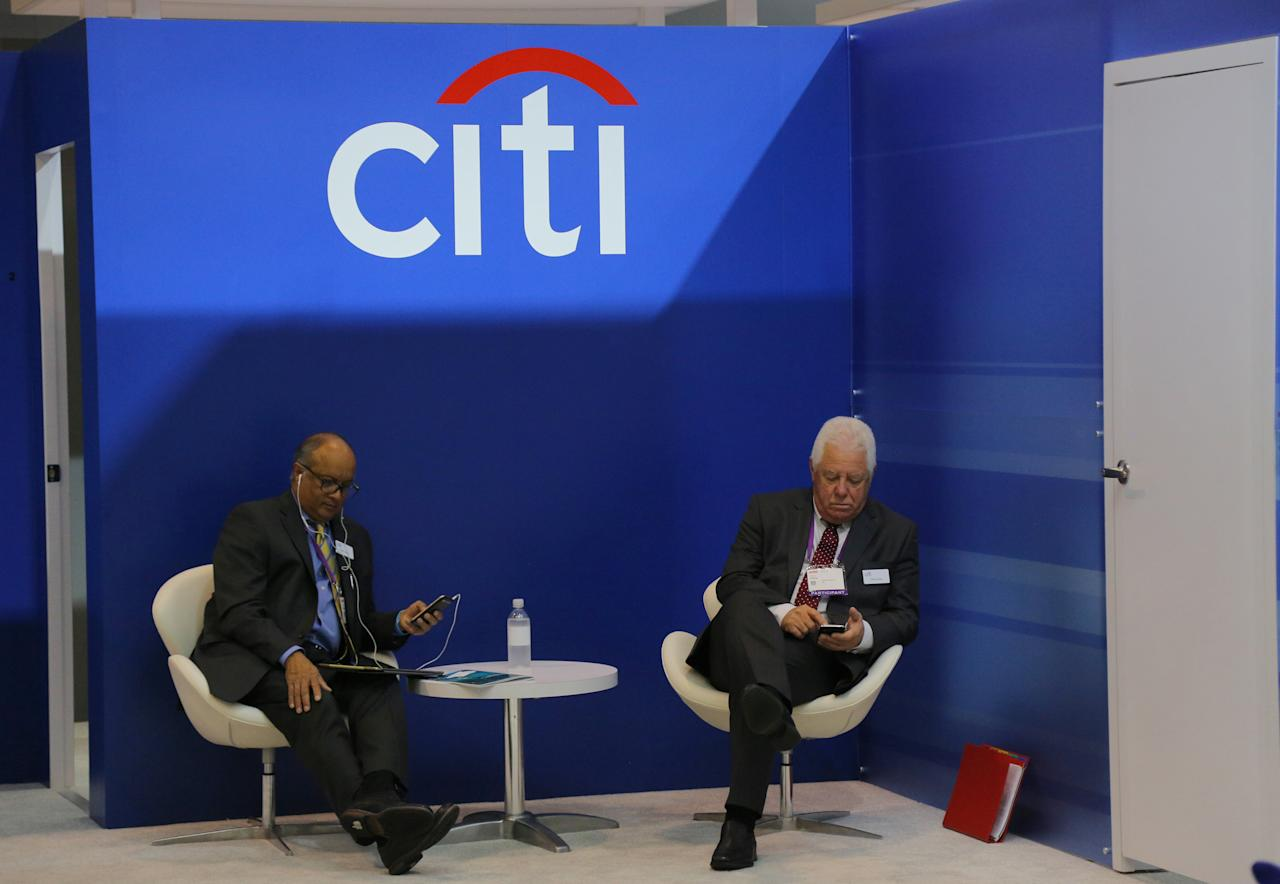 Two men look at their mobile phones under the Citigroup Inc (Citi) logo at the SIBOS banking and financial conference in Toronto, Ontario, Canada October 19, 2017. Picture taken October 19, 2017. REUTERS/Chris Helgren