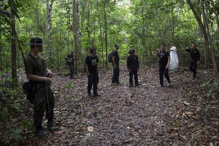 Members of a police forensic team carry a body bag with human remains dug from the grave near the abandoned human trafficking camp in the jungle close the Thailand border at Bukit Wang Burma in northern Malaysia
