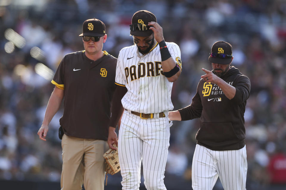 San Diego Padres shortstop Fernando Tatis Jr., center, walks off the field with manager Jayce Tingler, right, after diving for a ball in the fifth inning of a baseball game against the Cincinnati Reds, Saturday, June 19, 2021, in San Diego. (AP Photo/Derrick Tuskan)