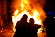 <p>SENSITIVE MATERIAL. THIS IMAGE MAY OFFEND OR DISTURB Demonstrators pose with a police riot shield in front of a burning police vehicle during a protest against a new proposed policing bill, in Bristol, Britain, March 21, 2021. REUTERS/Peter Cziborra</p>