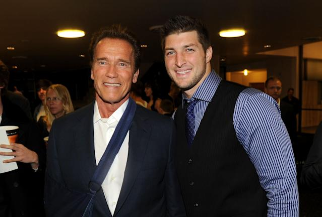 "HOLLYWOOD, CA - FEBRUARY 13: Former Governor of California Arnold Schwarzenegger (L) and NFL Player Tim Tebow of the Denver Broncos arrive at the premiere of Relativity Media's ""Act Of Valor"" held at ArcLight Cinemas on February 13, 2012 in Hollywood, California. (Photo by Jason Merritt/Getty Images for Relativity Media)"