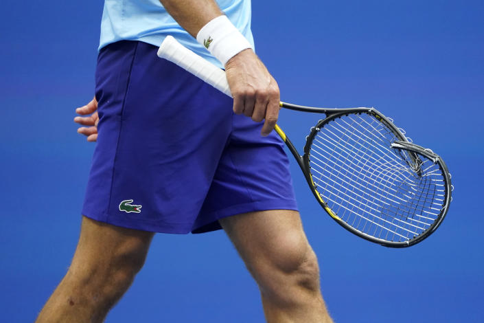 Novak Djokovic, of Serbia, walks back to his bench to replace his racket after smashing it upon losing a point to Daniil Medvedev, of Russia, during the men's singles final of the US Open tennis championships, Sunday, Sept. 12, 2021, in New York. (AP Photo/John Minchillo)