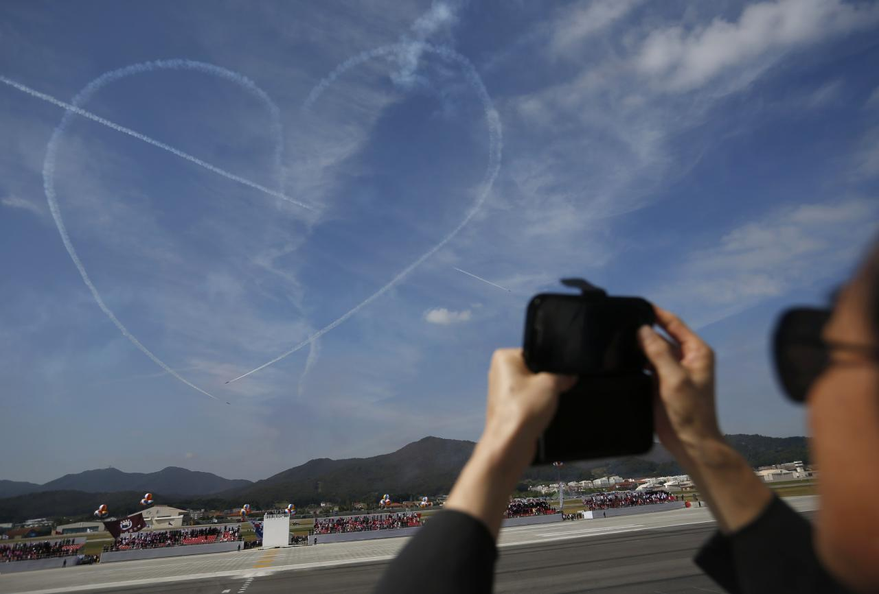 A man takes photographs of a heart-shaped contrail left in the sky by the Black Eagles South Korean Air Force aerobatic team during celebrations to mark the 65th anniversary of Korea Armed Forces Day, at a military airport in Seongnam, south of Seoul, October 1, 2013. REUTERS/Kim Hong-Ji (SOUTH KOREA - Tags: MILITARY ANNIVERSARY)