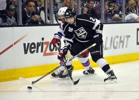 Jun 7, 2014; Los Angeles, CA, USA; Los Angeles Kings defenseman Slava Voynov (26) battles for the puck with New York Rangers center Brad Richards (19) in the second period during game two of the 2014 Stanley Cup Final at Staples Center. Mandatory Credit: Gary A. Vasquez-USA TODAY Sports