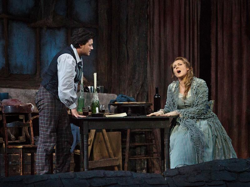 """In this photo provided by the Metropolitan Opera, Vittorio Grigolo portrays Rodolfo with Kristine Opolais as Mimi in the Metropolitan Opera's Live in HD broadcast of Puccini's """"La Boheme,"""" Saturday, April 5, 2014 in New York. Opolais made Metropolitan Opera history Saturday, stepping in for an ailing soprano to make her second company role debut in a span of 24 hours. On Friday night, Opolais sang Cio-Cio-San in Puccini's """"Madama Butterfly."""" (AP Photo/Metropolitan Opera, Marty Sohl)"""