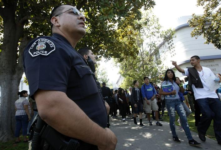 """LAUSD Police Officer Jay Cueva watches as students get out of Manual Arts High School. <span class=""""copyright"""">(Los Angeles Times)</span>"""