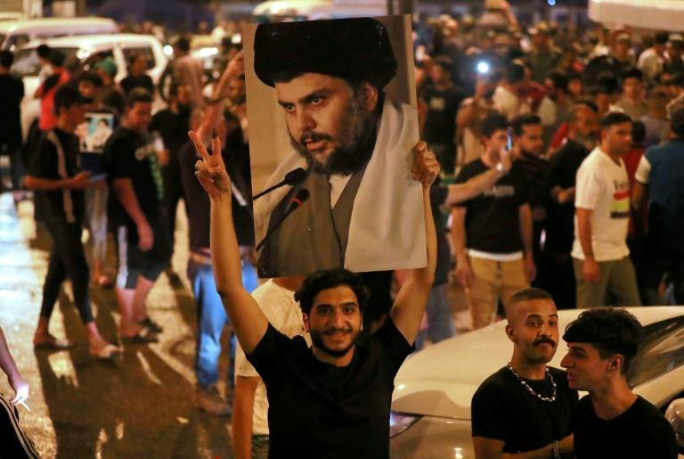 Supporters of Iraqi Shiite cleric Moqtada Sadr celebrate in Baghdad's Tahrir square on Monday after the announcement of parliamentary election results (AFP/AHMAD AL-RUBAYE)