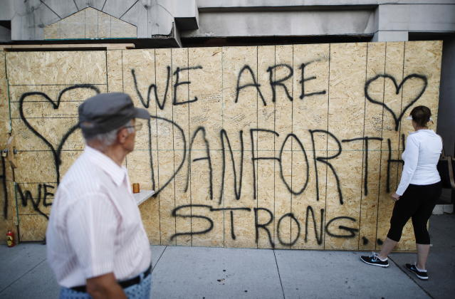 <p>People leave personal messages on a building under renovation, remembering the victims of Sunday's shooting on and near Danforth Avenue in Toronto on Monday, July 23, 2018. (Photo: Mark Blinch/The Canadian Press via AP) </p>