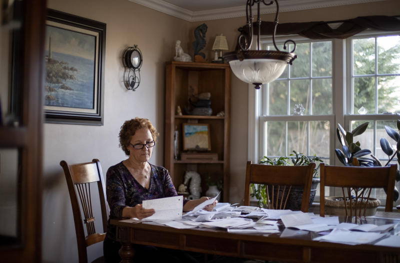 """Janet Uhlar sits at her dining room table with letters and photos she received through her correspondence with imprisoned Boston organized crime boss James """"Whitey"""" Bulger, Friday, Jan. 31, 2020, in Eastham, Mass. Although much had been written about the CIA's mind control experiments before Bulger's trial, Uhlar said she knew nothing about them until she began corresponding with the renowned gangster following his conviction in the fall of 2013. (AP Photo/David Goldman)"""
