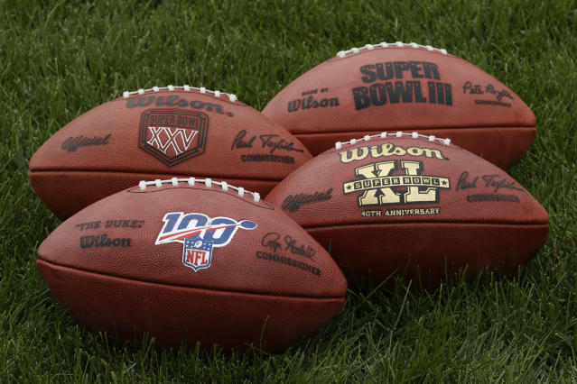 In this Oct. 17, 2019, photo footballs are displayed at the Philadelphia Eagles's NFL football training facility in Philadelphia. Those shiny NFL 100 logos on all the footballs being used to commemorate the leagues centennial season are part of a lengthy process that goes into making each handcrafted leather game ball. Wilson has been the official game ball of the NFL since 1941. The size, shape and feel of the football have evolved over the years, but the personal touch remains the same. (AP Photo/Matt Rourke)
