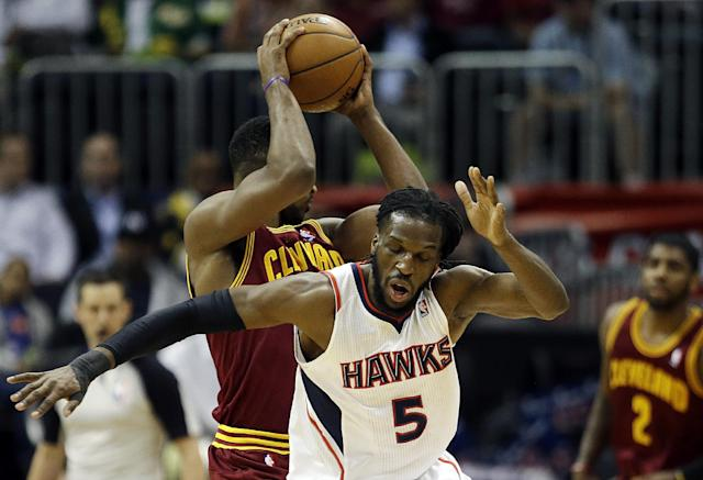 Cleveland Cavaliers' Tristan Thompson, rear, pulls the ball away from the reach of Atlanta Hawks' DeMarre Carroll in the first quarter of an NBA basketball game, Friday, April 4, 2014, in Atlanta. (AP Photo/David Goldman)
