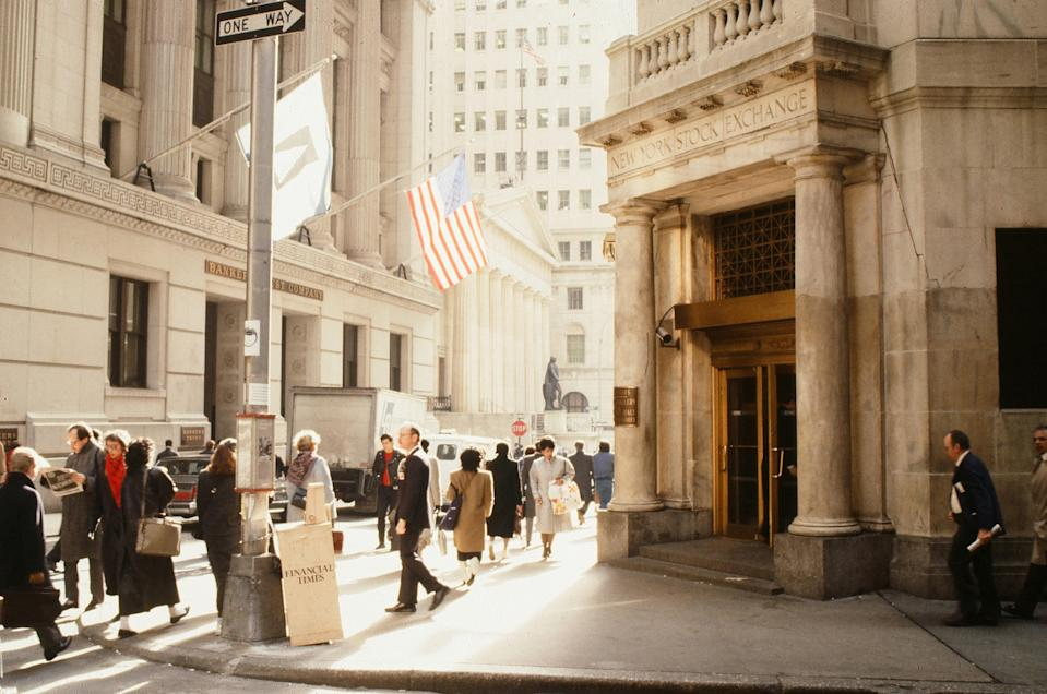Pedestrians walk past the entrance to the New York Stock Exchange on Wall Street. The 1980s was a decade marked by opulence, particularly in New York City—a trend that held firm right up until the stock market crash of 1987.