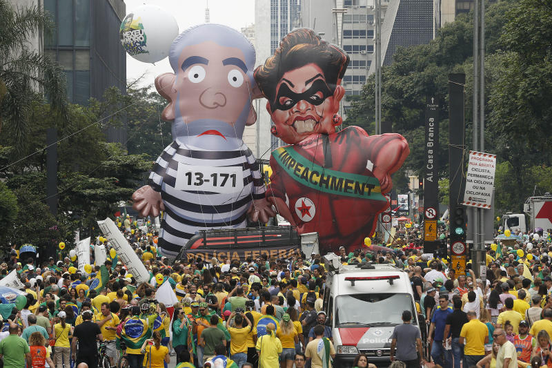 "FILE - In this March 13, 2016 file photo, demonstrators parade large inflatable dolls depicting Brazil's former President Luiz Inacio Lula da Silva in prison garb and President Dilma Rousseff dressed as a thief, with a presidential sash that reads, ""Impeachment,"" in Sao Paulo, Brazil. Silva is facing several corruption charges, Brazil's largest-ever graft probe has decimated the political party he founded and Rousseff, his hand-picked successor was impeached and ousted from office. Yet Silva is topping polls for the 2018 presidential race. (AP Photo/Andre Penner, File)"