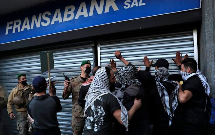 A Lebanese army officer, center, pushes back protesters who were trying to break a bank door, during a protest demanding that local banks allow them to withdraw their money  - Hussein Malla /AP