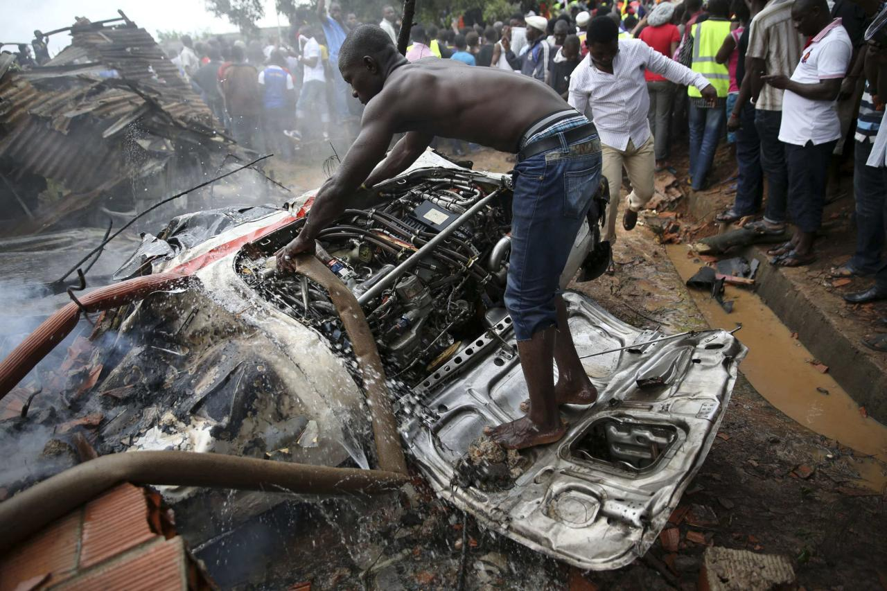 A man tries to extinguish a fire from the engine of a plane at the site of a plane crash near the Lagos international airport October 3, 2013. Fifteen people were killed when an Embraer passenger plane crashed shortly after take-off just outside Lagos airport's domestic terminal on Thursday, Nigerian authorities said. REUTERS/Akitnunde Akinleye (NIGERIA - Tags: DISASTER SOCIETY)