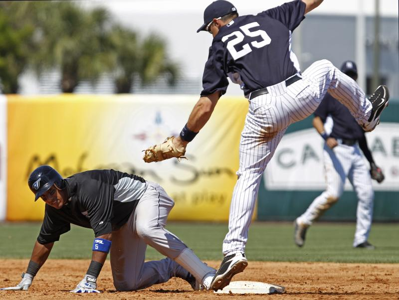 Leaping after fielding a high throw from Eduardo Nunez, New York Yankees first baseman Mark Teixeira (25) tries to tag Toronto Blue Jays Yunel Escobar, who  is safe returning to second after trying to stretch a sixth-inning double into a triple in the Blue Jays spring training baseball game against the New York Yankees at Steinbrenner Field in Tampa, Fla., Saturday, March 19, 2011.  The game ended in a 5-5 tie. (AP Photo/Kathy Willens)