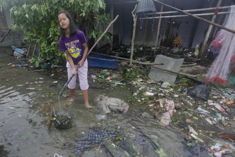 A Thai girl cleans up in the aftermath of Tropical Storm Pabuk Saturday, Jan. 5, 2019, in Pak Phanang in Thailand's southern province of Nakhon Si Thammarat. The storm damaged houses, knocked down power lines and triggered flash floods in several east coast provinces. (AP Photo/Sumeth Panpetch)