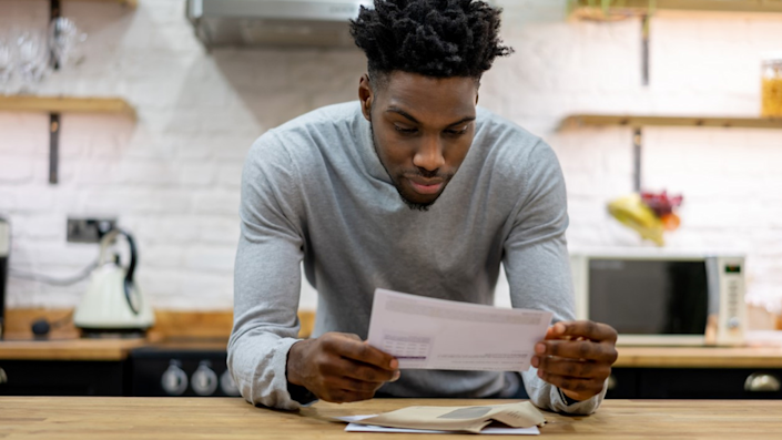 Man in kitchen looking at paper bill