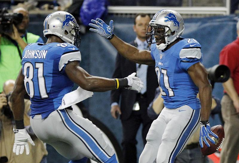 Detroit Lions wide receiver Calvin Johnson (81) congratulates running back Reggie Bush after Bush's 14-yard touchdown during the first quarter of an NFL football game against the Baltimore Ravens in Detroit, Monday, Dec. 16, 2013. (AP Photo/Duane Burleson)