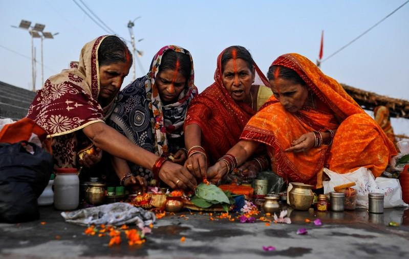 Hindu devotees pray on the banks of Sarayu river after Supreme Court's verdict on a disputed religious site, in Ayodhya