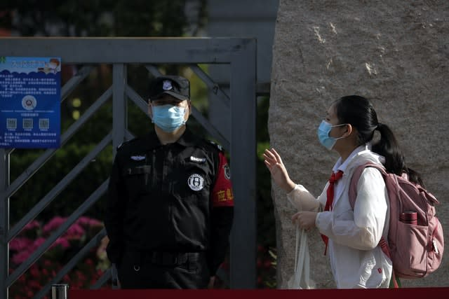 A student wearing a protective face mask to help curb the spread of the new coronavirus waves to teachers as she arrives for the reopening of a primary school in Beijing