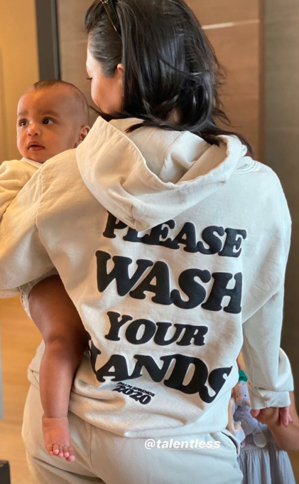 Kourtney Kardashian holding Psalm West in a Talentless jumper