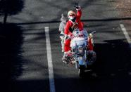 A man dressed in Santa Claus costume rides his motorbike during Xmas Toy Run parade amid the coronavirus disease (COVID-19) outbreak, in Tokyo