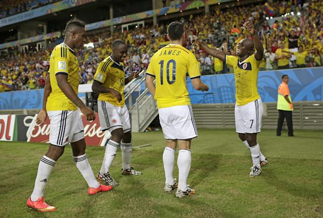 Colombia's James Rodriguez (10) celebrates with teammate Colombia's Pablo Armero, right after scoring during the group C World Cup soccer match between Japan and Colombia at the Arena Pantanal in Cuiaba, Brazil, Tuesday, June 24, 2014. (AP Photo/Felipe Dana)