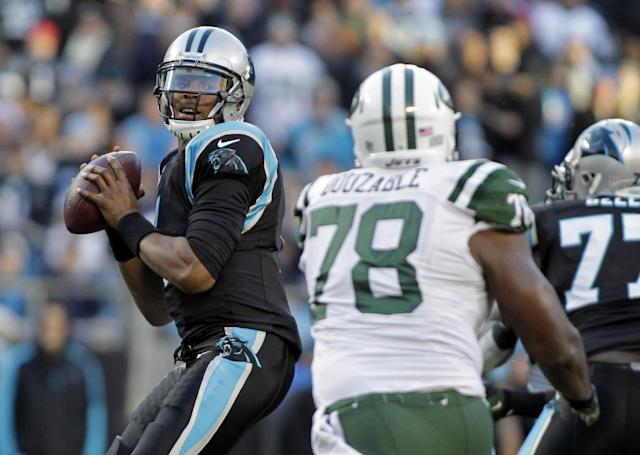 Carolina Panthers quarterback Cam Newton, left, looks to pass under pressure from New York Jets' Leger Douzable (78) during the first half of an NFL football game in Charlotte, N.C., Sunday, Dec. 15, 2013. (AP Photo/Bob Leverone)