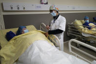 Surgeon Lara Ribeiro Parenti, right, talks to Caroline Erganian, prior to her surgery at Bichat Hospital, AP-HP, in Paris, Wednesday, Dec. 2, 2020. Erganian, 58, hopes to shed more than a third of her weight as a result of having a large part of her stomach cut out and be free of knee and back pain — and of her cane. She prayed in the final weeks that her phone wouldn't ring with news of another delay. (AP Photo/Francois Mori)