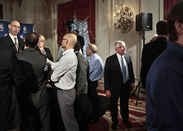 NBA Deputy Commissioner Adam Silver, far left, speaks with reporters as NBA Commissioner David Stern, third from right, leaves after a press conference at the NBA board of governors meeting, Wednesday, Oct. 23, 2013 in New York. Stern will formally step aside on Feb. 1, 2014, after 30 years and Silver will become the new league commissioner. (AP Photo/Bebeto Matthews)