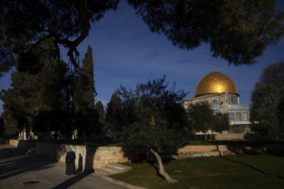 A Muslim woman walks near the Dome of the Rock Mosque in the Al Aqsa Mosque compound in Jerusalem's Old City, Monday, Feb. 8, 2021. (AP Photo/Oded Balilty)