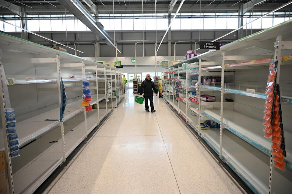 A shopper walks past empty toilet roll shelves amidst the novel coronavirus COVID-19 pandemic, in Manchester, northern England on March 20, 2020. - The British prime minister urged people in his daily press conference on March 19 to be reasonable in their shopping as supermarkets emptied out of crucial items -- notably toilet roll -- across Britain. The government said it was temporarily relaxing elements of competition law to allow supermarkets to work together to maintain supplies. (Photo by Oli SCARFF / AFP) (Photo by OLI SCARFF/AFP via Getty Images)