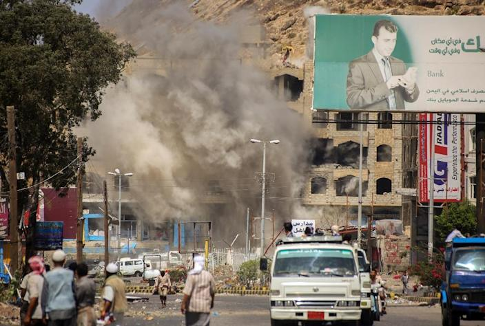 Smoke billows after a mortar shell hit a building in the Beer Basha area of Taez, southern Yemen, on March 12, 2016 (AFP Photo/Ahmad al-Basha)