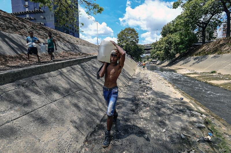 The quest for drinkable water has rapidly become an obsession for millions in Caracas days after a crippling power blackout stalled the city's pumps (AFP Photo/JUAN BARRETO)