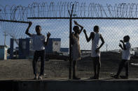 Youths stand at a gate along the seashore in the La Saline neighborhood of Port-au-Prince, Haiti, Monday, July 19, 2021. The country of more than 11 million people are still reeling from the July 7 killing of President Jovenel Moise. (AP Photo/Matias Delacroix)