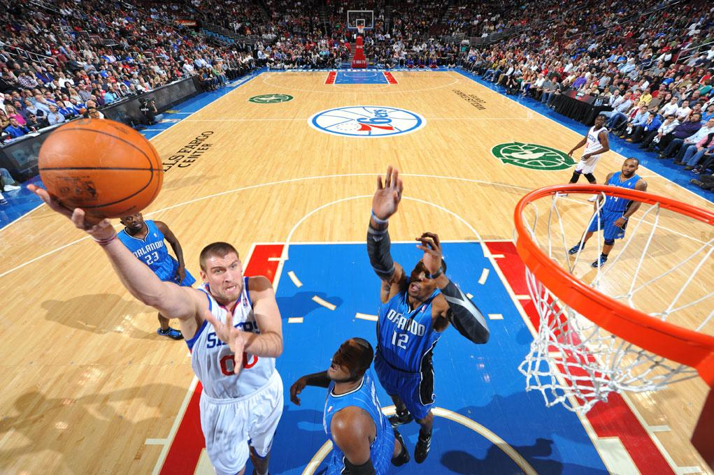 PHILADELPHIA, PA - APRIL 7: Spencer Hawes #00 of the Philadelphia 76ers goes to the basket over Glen Davis #11 and  Dwight Howard #12 of the Orlando Magic on April 7, 2012 at the Wells Fargo Center in Philadelphia, Pennsylvania.    NOTE TO USER: User expressly acknowledges and agrees that, by downloading and/or using this Photograph, user is consenting to the terms and conditions of the Getty Images License Agreement. Mandatory Copyright Notice: Copyright 2012 NBAE