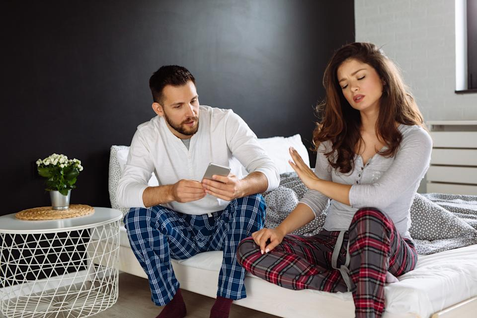 Dissatisfied young brunette arguing with boyfriend over smart phone