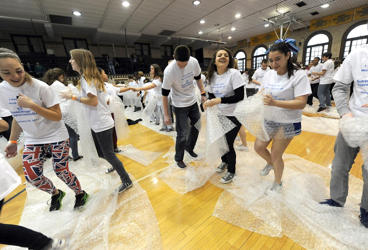 IMAGE DISTRIBUTED FOR SEALED AIR CORPORATION - Hawthorne High School students set a Guinness World Record for the most people popping Bubble Wrap at one time to celebrate the 13th annual Bubble Wrap Appreciation Day, Monday, Jan. 28, 2013, in Hawthorne, NJ, the town of Bubble Wrap's birthplace. 366 students popped more than 8,000 square feet of Bubble Wrap in two minutes to the set the record. (Photo by Diane Bondareff/Invision for Sealed Air Corporation/AP Images)