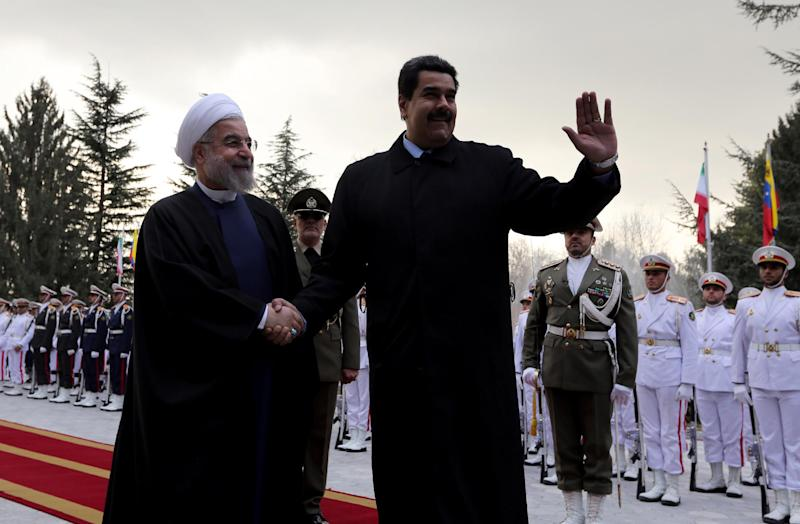 Iranian President Hassan Rouhani (left) shakes hands with Venezuelan President Nicolas Maduro after reviewing the honor guard at the Saadabad Palace in Tehran on January 10, 2015